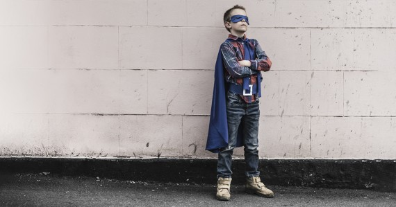 young boy in superhero cape costume