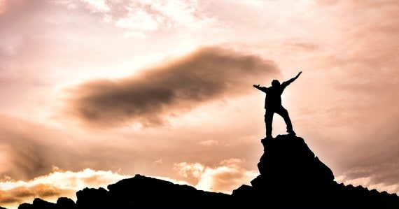 silhouetted man raising hands in victory at sunset on a rocky outcrop